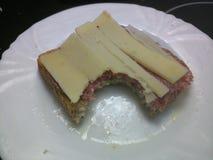 Põe manteiga fatias e chouriço do queijo Cheddar em uma fatia de pão Fotos de Stock Royalty Free