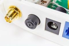 Põe o botão com antena e conectores de alimentação no painel traseiro do close up do roteador fotografia de stock