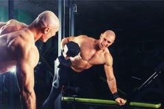 Põe o indivíduo atlético, execute a imprensa do exercício com pesos, no salão de esporte foto de stock
