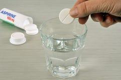 Põe um selo de aspirin em um vidro da água imagens de stock