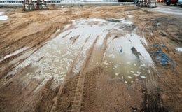 Pöl och gyttja med lastbilen rullar spåret på konstruktionsplatsen i regnig dag Royaltyfria Foton