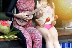 Pölpartiet, lyckliga kvinnor tycker om att spela musikinstrumentet, genom simbassängen, flickvänner i bikinileende och att skratt royaltyfri fotografi
