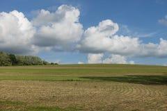 Pösig vit fördunklar över en lantgårdbacke arkivbilder
