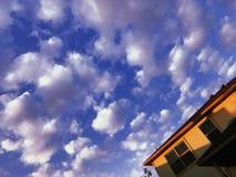 Pösiga vita moln på en blå himmel i förorterna arkivfoto