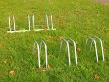 Público esvazie o suporte para bicicletas na grama Quadro do ferro cinzento com marcas da corrosão imagens de stock royalty free