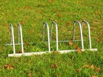 Público esvazie o suporte para bicicletas na grama Quadro do ferro cinzento com marcas da corrosão imagens de stock