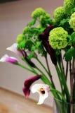 Púrpura borrosa y con las flores en el florero Fotos de archivo libres de regalías