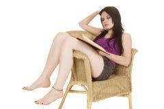 Púrpura de la mujer en la lectura de la silla imagenes de archivo