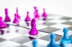 Púrpura y caballero azul que luchan en un tablero de ajedrez imagen de archivo