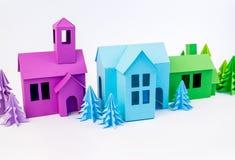 Púrpura y casa verde azul pegadas fuera de los soportes de papel en el bosque violeta imagenes de archivo