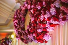Púrpura y rojo florece la guirnalda de la recepción nupcial Imagen de archivo
