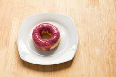 Pączek z czarnej jagody polewą w bielu talerzu na drewnianym tle Obraz Royalty Free