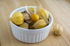 Pęcherzycy peruviana pęcherzycy jadalne smakowite owoc w białym naczyniu na drewnianym stole Obraz Royalty Free