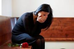 Płacz kobieta z czerwieni różą przy pogrzebem w kościół fotografia stock