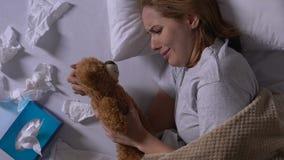 Płacz kobiety przytulenia miś, używać pieluchy na łóżku, samotność po łama w górę zbiory