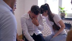 Płakać mężczyzna opowiada o problemach na grupowym terapii sesi obsiadaniu na krzesłach w okręgu zbiory wideo