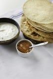 Płascy Indiańscy chleby z raita i mango chutney słuzyć na stole Fotografia Stock