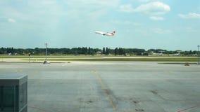 Płaski brać daleko, latający nad pasem startowym przy lotniskiem, widok od terminal przez drogę zbiory wideo