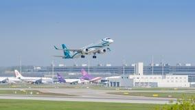 Płaski Embraer strumień Air Dolomiti linie lotnicze zyskuje wysokość zdjęcia stock