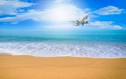 Płaski latanie na niebieskim niebie z obłocznym tłem nad plażą Obrazy Royalty Free