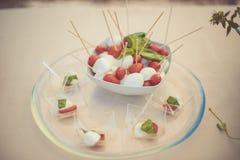 Płaski skład z piłkami mozzarella, czereśniowi pomidory i basil na, szklanej tacy i beżu tle Obraz Royalty Free