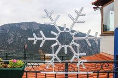 Płatek śniegu Bożenarodzeniowa dekoracja na ogrodzeniu w Delphi Grecja dachówkowym dachem, balkonową przegapia głęboką dolina i g obraz stock