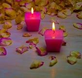 Płatki i palenie różowe świeczki na drewnianym tle obrazy stock