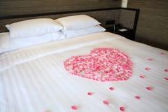 Płatki róże na białym miesiąca miodowego łóżku zdjęcie stock