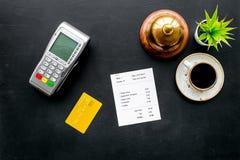 Płatniczy śmiertelnie na restauracyjnego biurka pobliskim rachunku, usługowy dzwon, kawa na czarnego tła odgórnym widoku zdjęcia royalty free