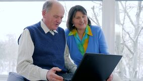Płatniczy online nowożytni starzy ludzie, szczęśliwy mąż i żona, opowiadają w skype z komputerem w domu zdjęcie wideo