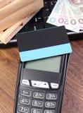 Płatniczy terminal z kredytową kartą, połysku pieniądze, laptopem i zawijającymi pudełkami na drewnianym barłogu, Obrazy Royalty Free