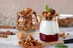 Płatowaty śniadanie z granola, jogurtem i dżemem w szklanym słoju, zdjęcie stock