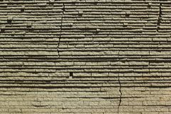 Płatowaty kamiennej ściany tło z pęknięciami obraz stock