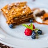 Płatowaty miodowy tort na bielu talerzu z jagodami zdjęcie stock