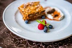 Płatowaty miodowy tort na bielu talerzu z jagodami obraz royalty free