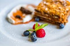 Płatowaty miodowy tort na bielu talerzu z jagodami obraz stock