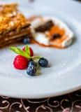 Płatowaty miodowy tort na bielu talerzu z jagodami obrazy stock