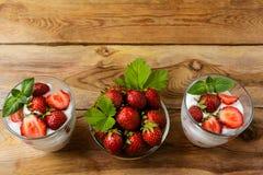 Płatowaty truskawki diety jogurtu deser na drewnianym tle obrazy stock