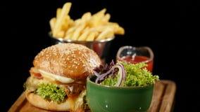 Płodozmienny hamburger z ketchupem nalewającym nad francuz sałatką i dłoniakami Czarny tło hamburger z francuzów dłoniakami i zbiory