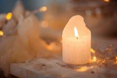 Płonąca świeczka na drewnianej powierzchni przeciw tłu bożonarodzeniowe światła, zdjęcie royalty free