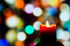 Płonąca świeczka na tle kolorowi okręgi Obrazy Royalty Free