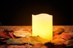 Płonąca świeczka otaczająca jesień liśćmi Obrazy Royalty Free