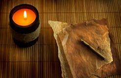 Płonąca świeczka z starymi papierami Obrazy Stock