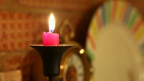 Płonąca czerwona świeczka w czarnych kandelabrach Stojaki na ceglanej grabie Zegary na tle zbiory wideo