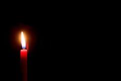 Płonąca czerwona świeczka z czarnym tłem Obrazy Stock