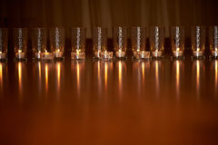 Płonące świeczki w przejrzystych szkłach, błyszcząca podłoga odbicie Nastrój, relaks, modlitwa i wygoda, zdjęcie stock