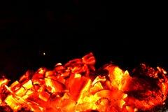 Płonący drewniani węgle i jeden latanie iskra zdjęcia stock