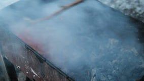 Płonący drewniany węgiel Kulinarny kurczaka mięso na gorącym węglu drzewnym przy zima wieczór Mężczyzna miesza węgle z kijem zbiory