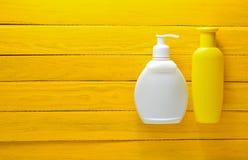Płukanka i sunblock na żółtych drewnianych deskach Akcesoria dla kurortu na morzu Obrazy Stock