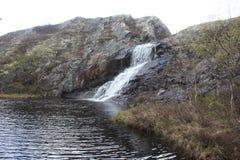 Płynąć w dół od skalistego brzeg w jeziorną rzekę zdjęcie royalty free